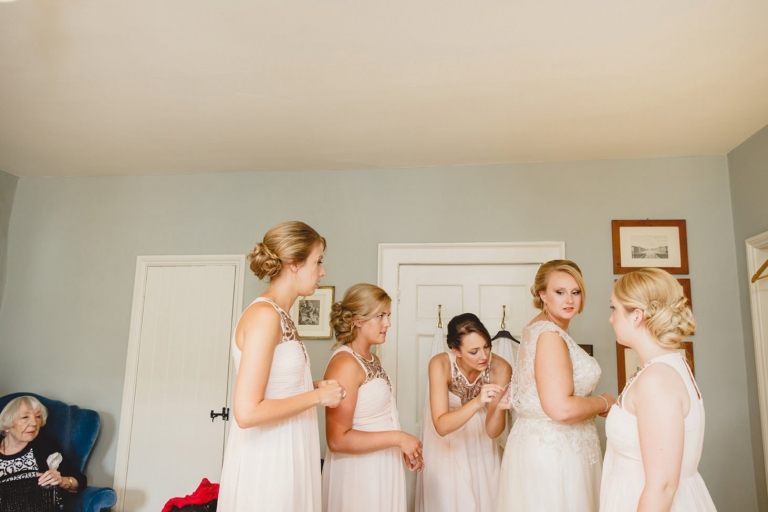 oxfordshire wedding photography brides dress being done up