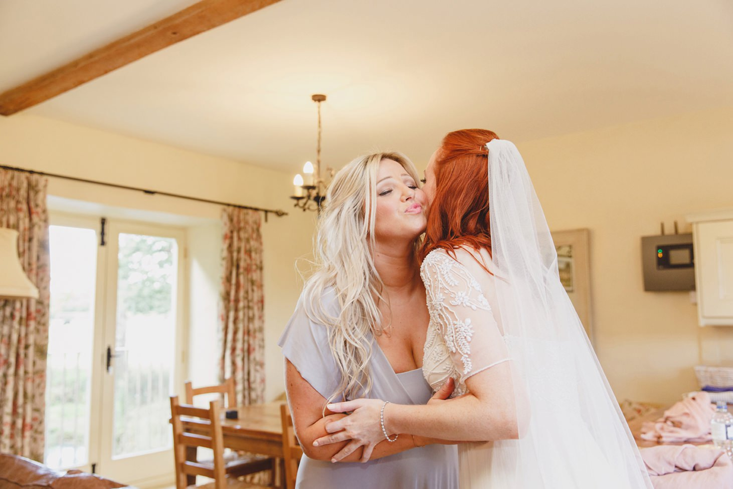 Caswell House wedding photography bride hugging bridesmaid