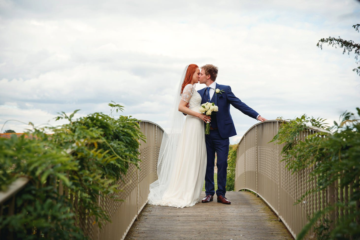 caswell house wedding photography bride and groom kissing on bridge