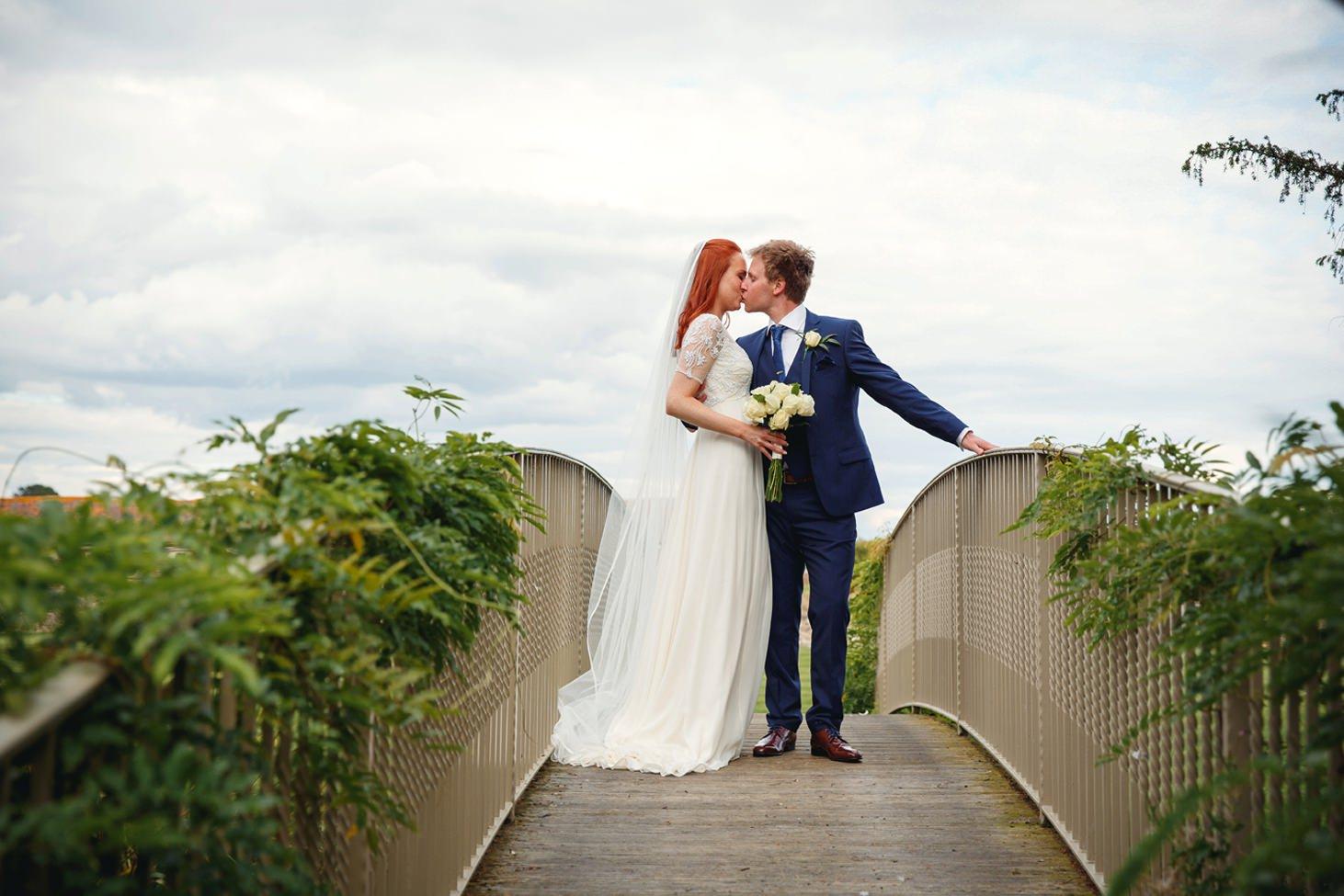 caswell house wedding photography bride and groom kissing on bridge