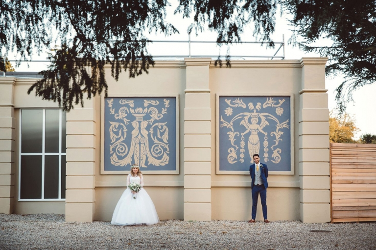 Down Hall hotel wedding photography bride and groom by wall