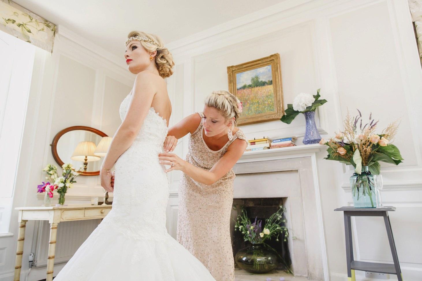 The Rectory Hotel Crudwell bridesmaids doing up wedding dress