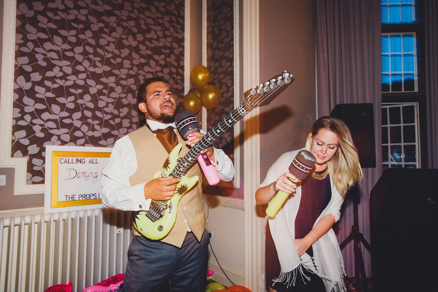 Wycombe Abbey wedding photography guests with blow up guitar