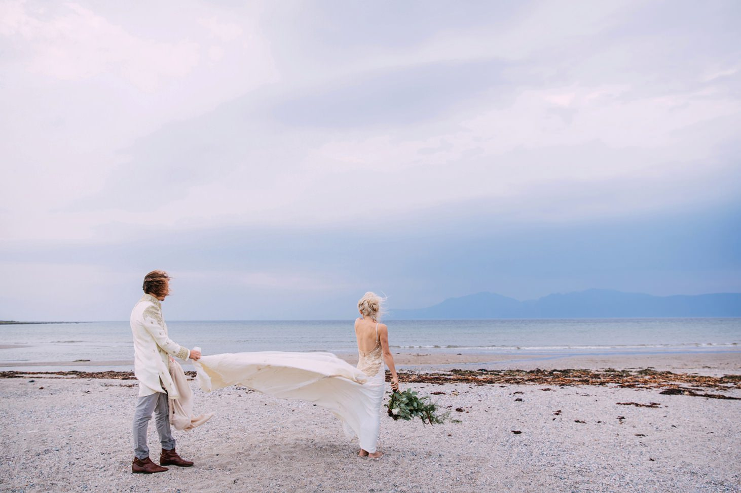 sle of bute wedding photography groom holding bride dress
