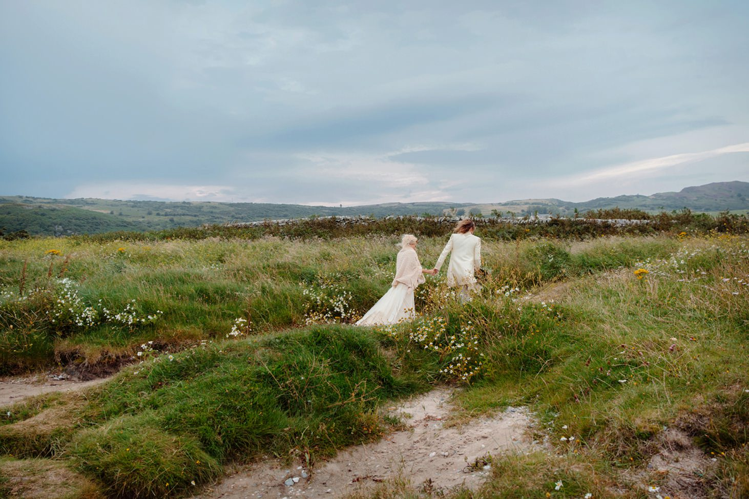 sle of bute wedding photography bride and groom walking through grass