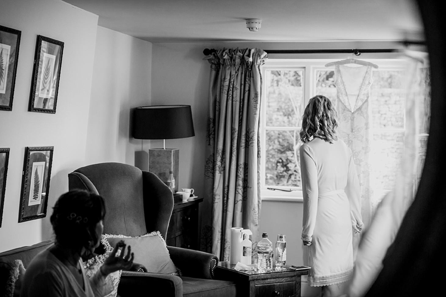 cotswolds wedding bride looking at wedding dress