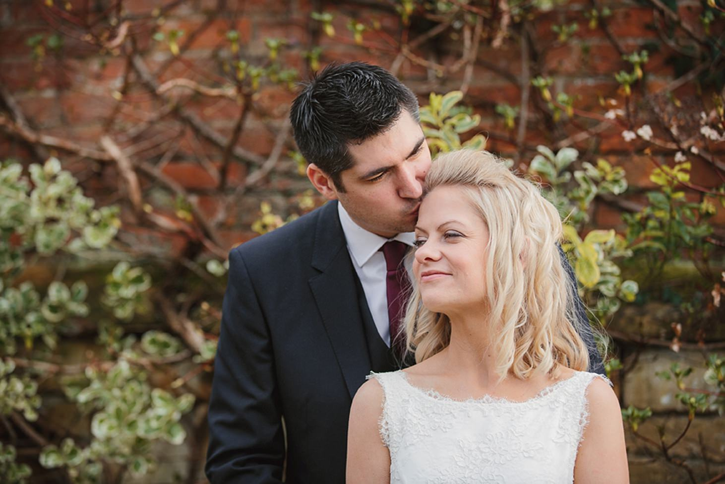 cotswolds wedding groom kisses bride