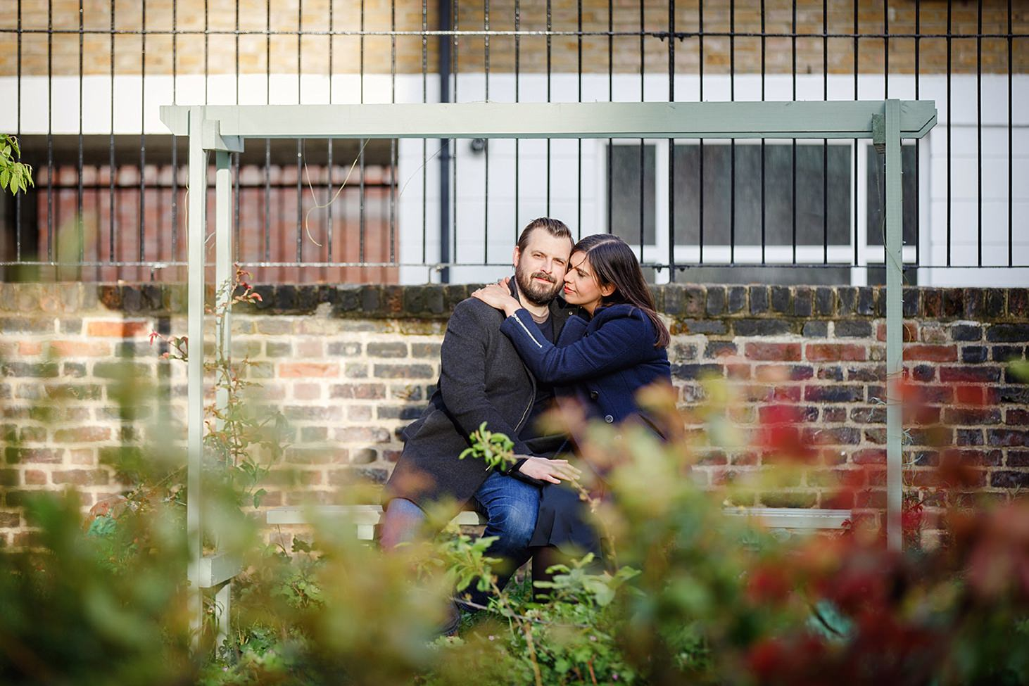 shoreditch engagement shoot couple hug on bench