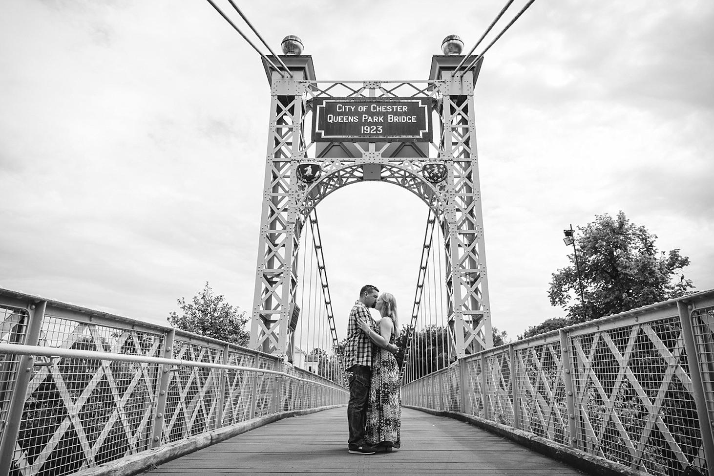 chester engagement shoot couple kiss on queens park bridge