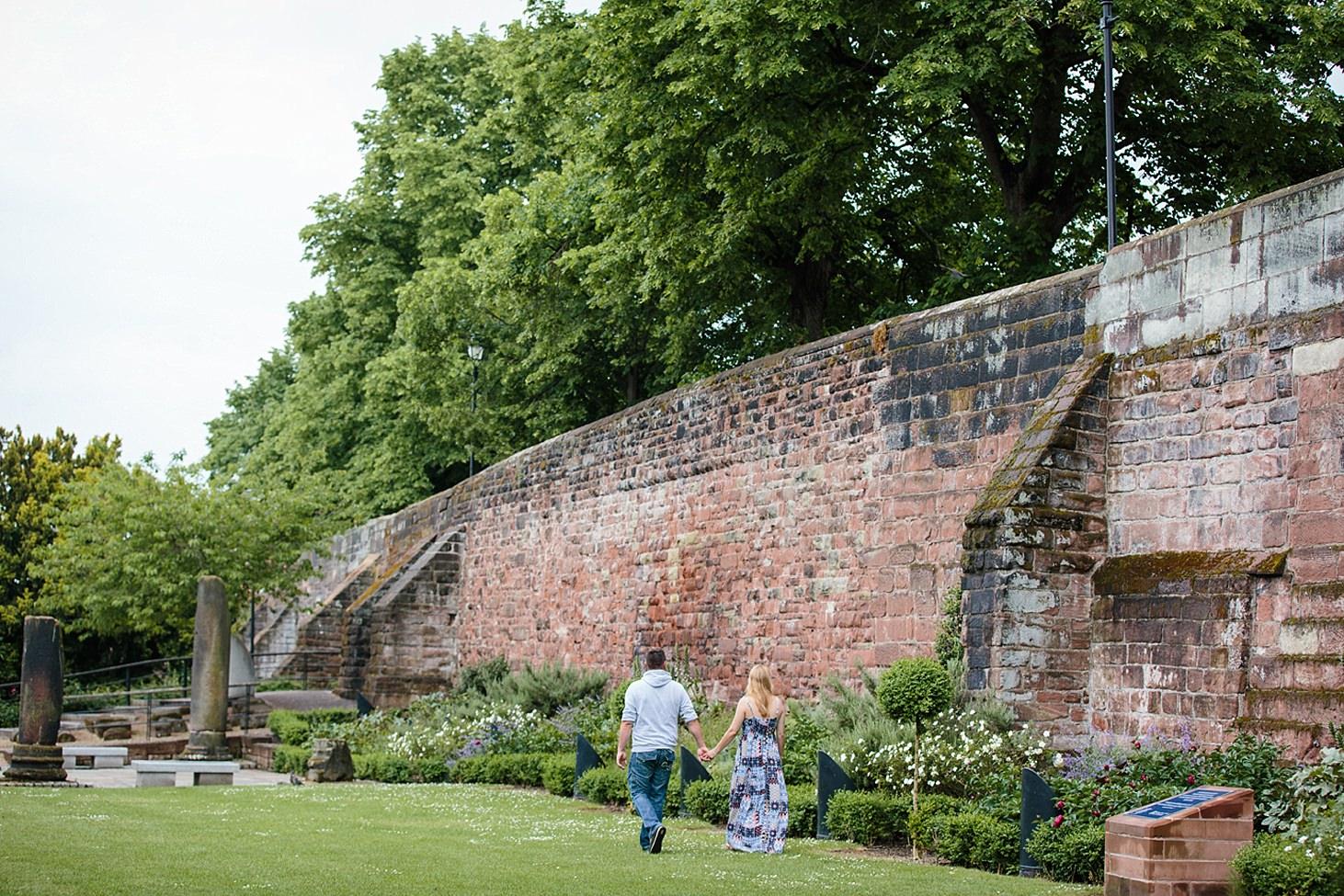 chester engagement shoot couple walking through gardens