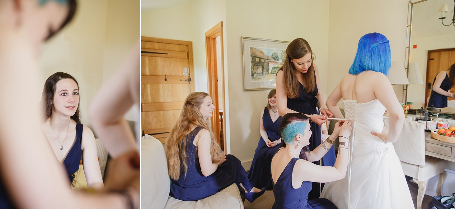 gate street barn wedding photography bridesmaids helping bride into dress