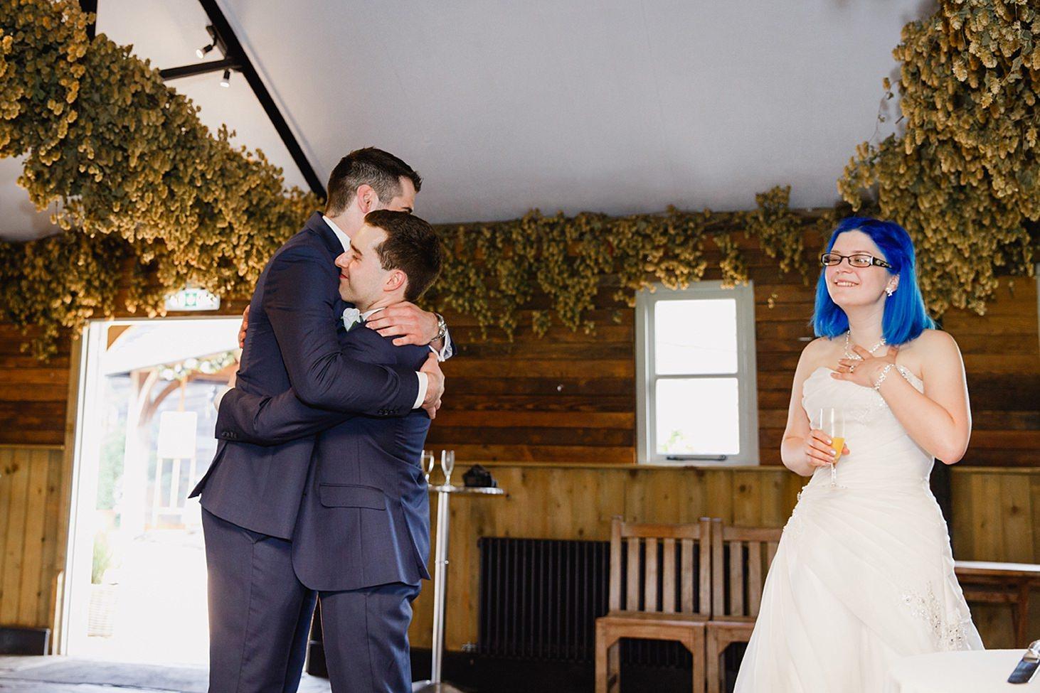 gate street barn wedding photography groom and best man hug