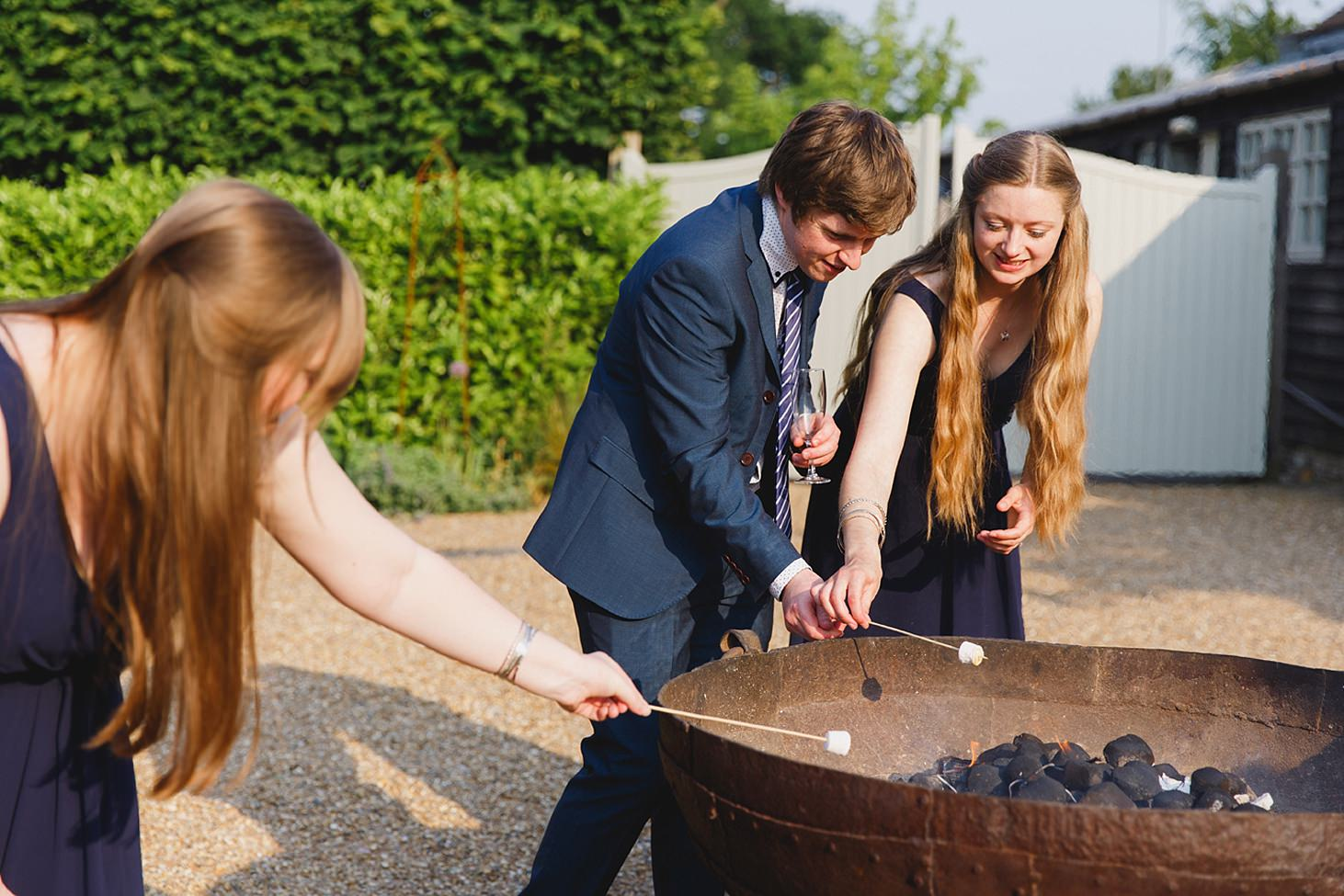gate street barn wedding photography guests roasting marshmallows