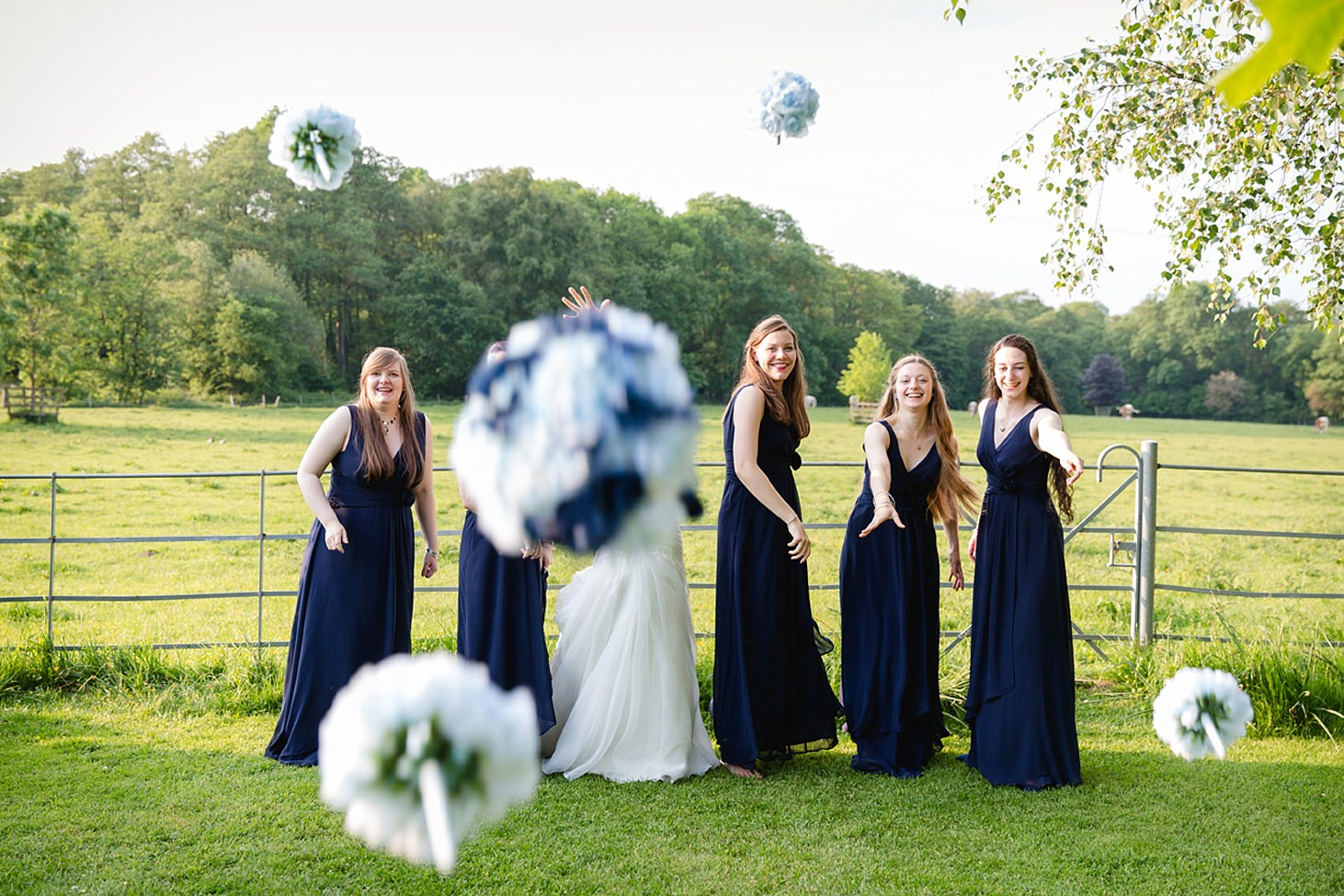 gate street barn wedding photography bride and bridesmaids throwing bouquets