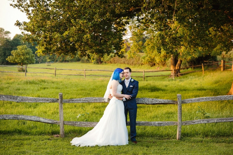 gate street barn wedding photography bride and groom by fence
