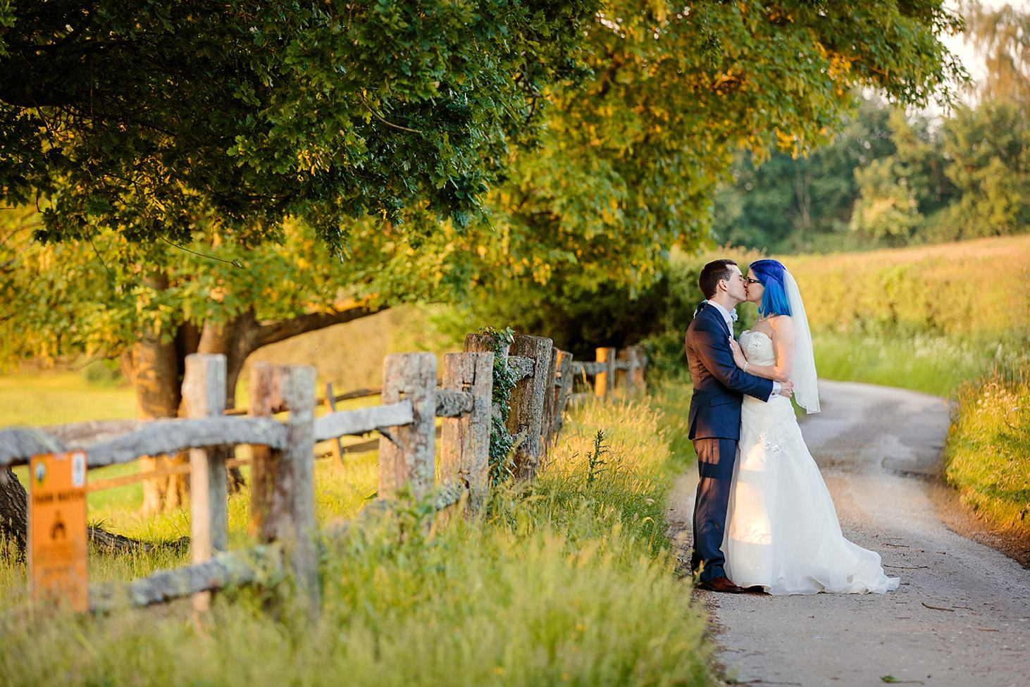 gate street barn wedding photography bride and groom kiss on pathway