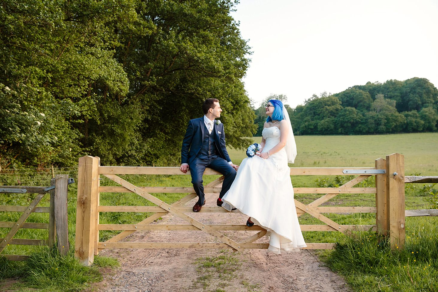 gate street barn wedding photography bride and groom sat on gate