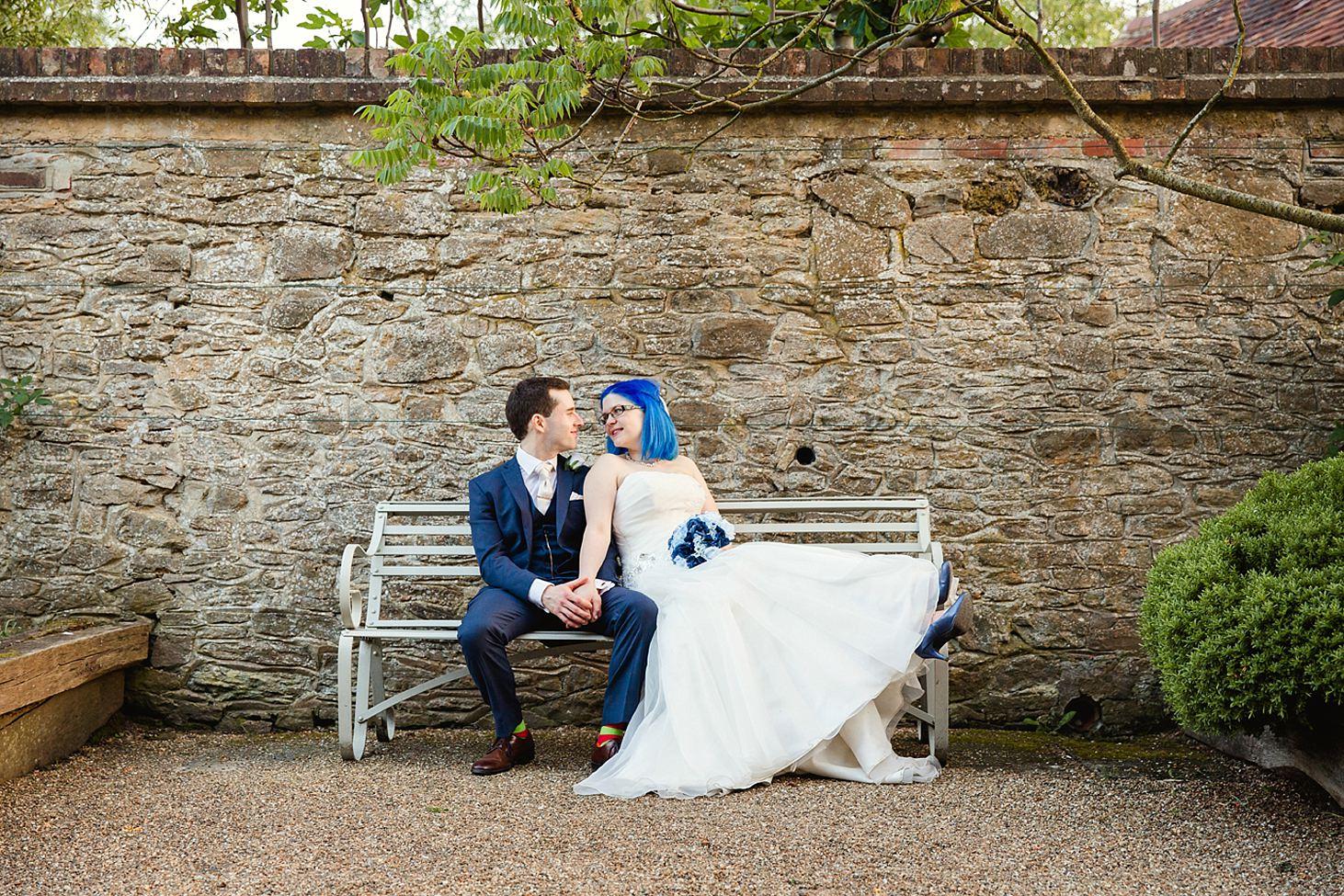 gate street barn wedding photography bride and groom sat on bench