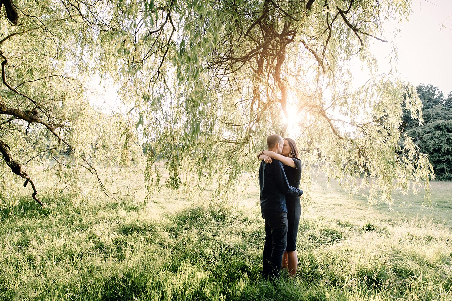 trent park engagement shoot couple kissing in willow tree