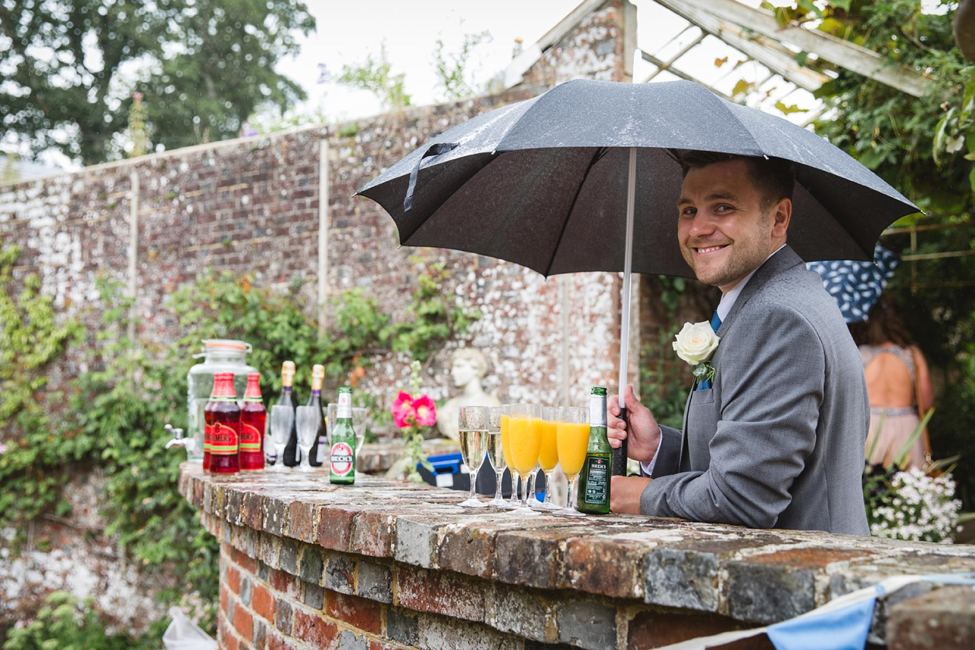 Bignor Park wedding photography groomsman with drinks