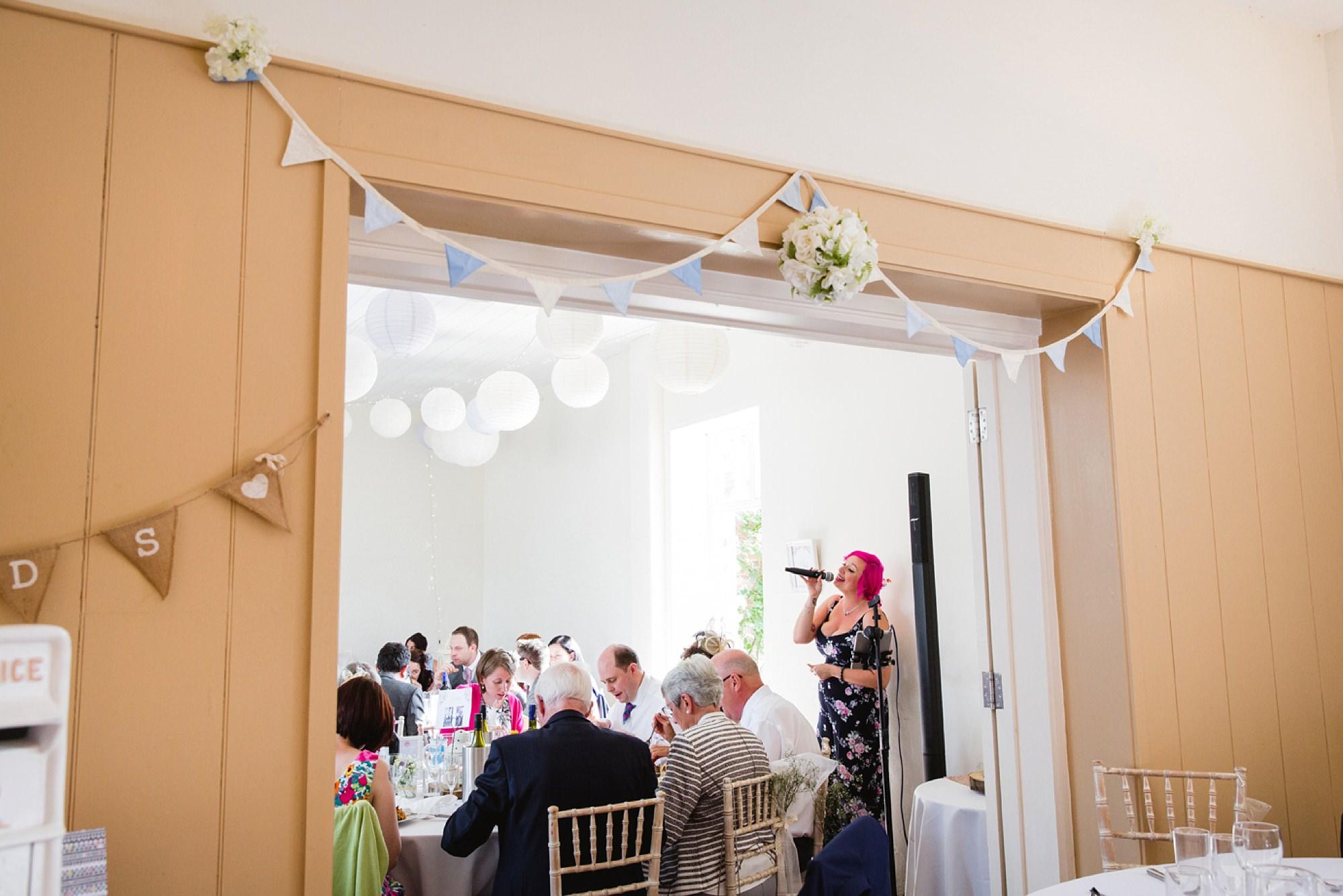 Bignor Park wedding photography singer during meal