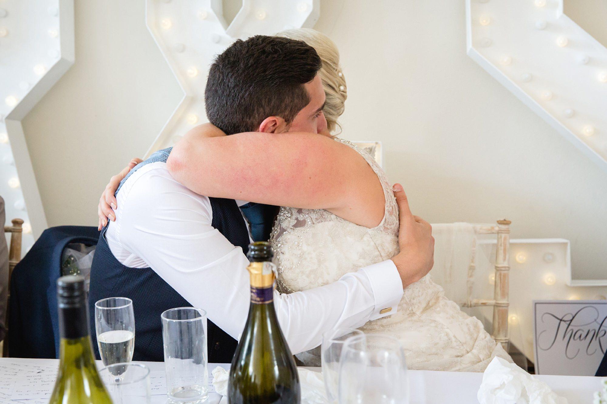Bignor Park wedding photography bride and groom hugging in speeches