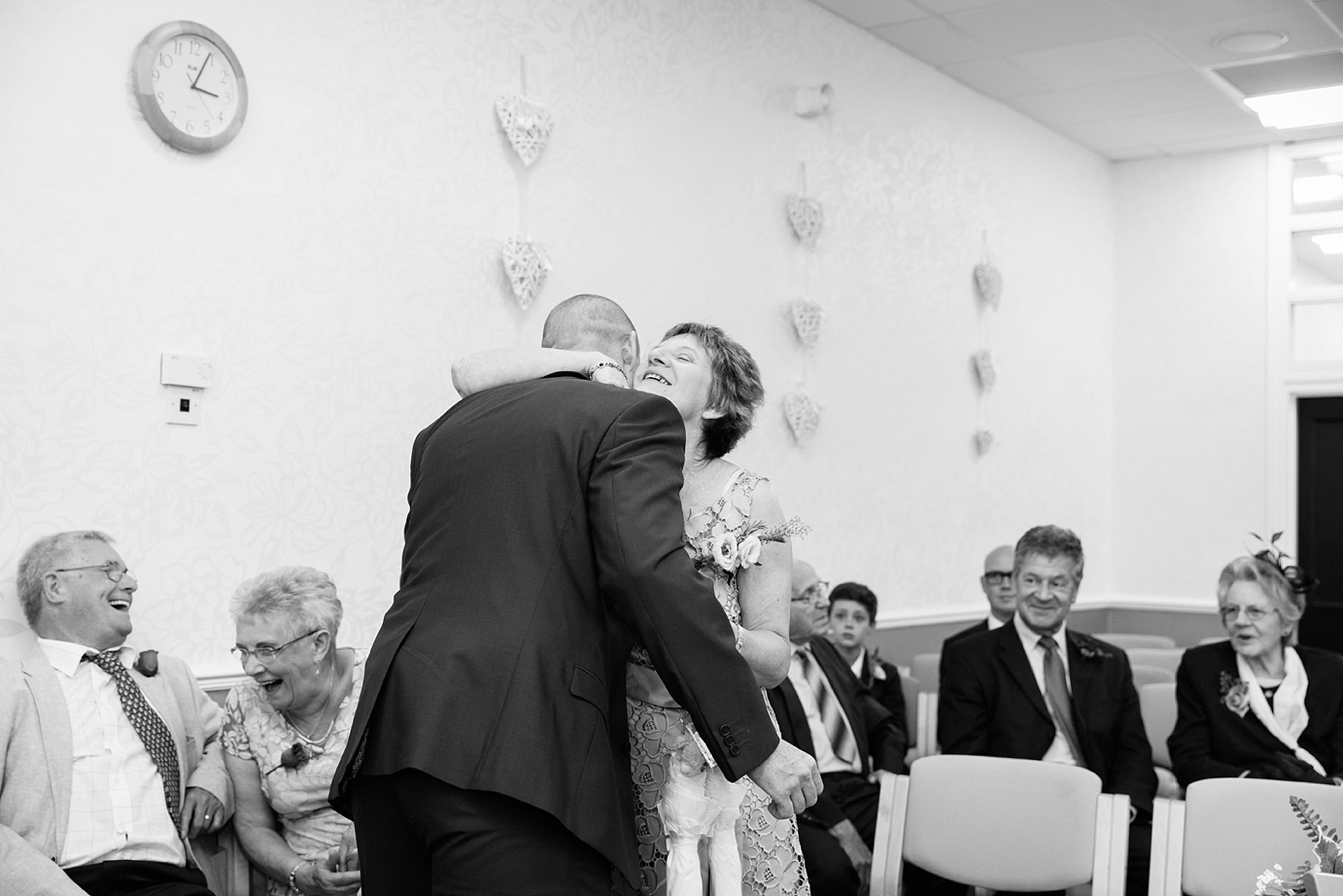 Mill House hotel wedding photography groom hugs guest