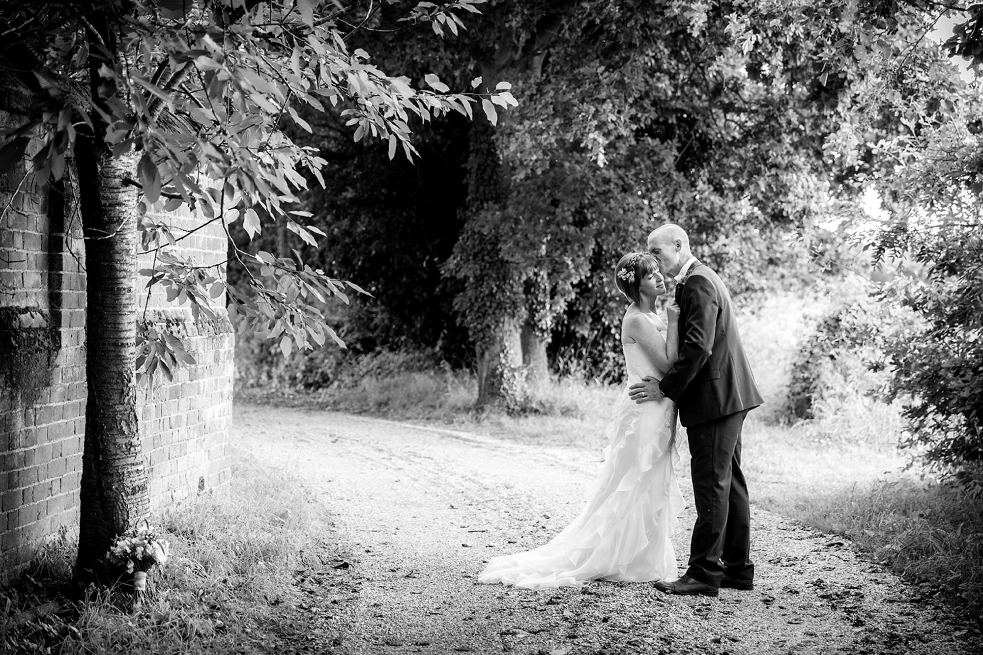 Mill House hotel wedding photography bride and groom kiss in gardens