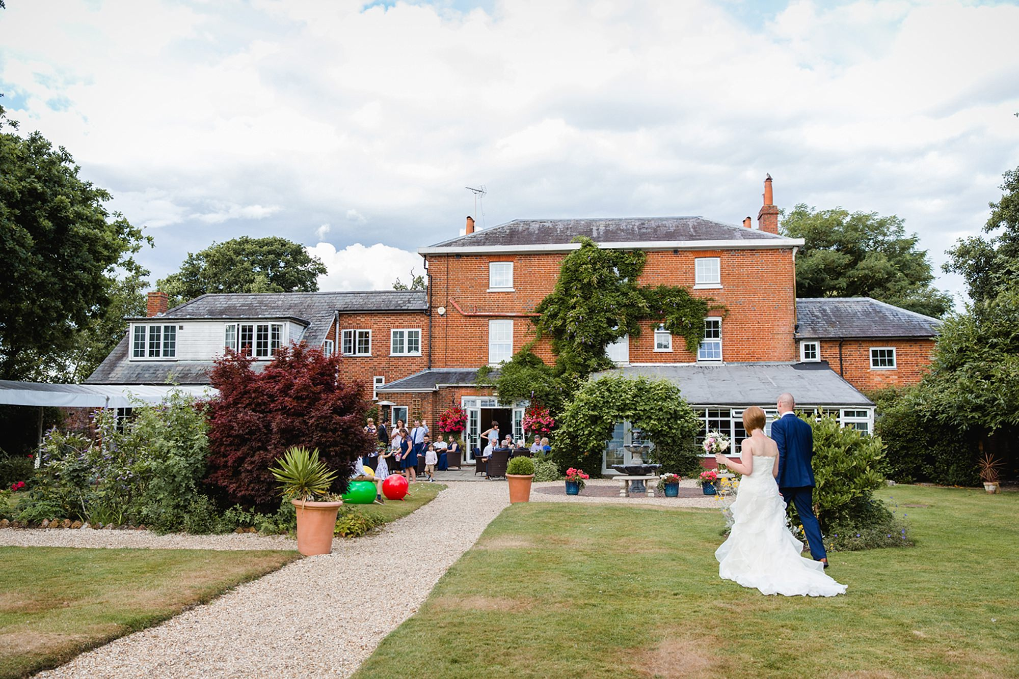 portrait of bride and groom kissing in the gardens at mill house hotel wedding bride and groom joining wedding party