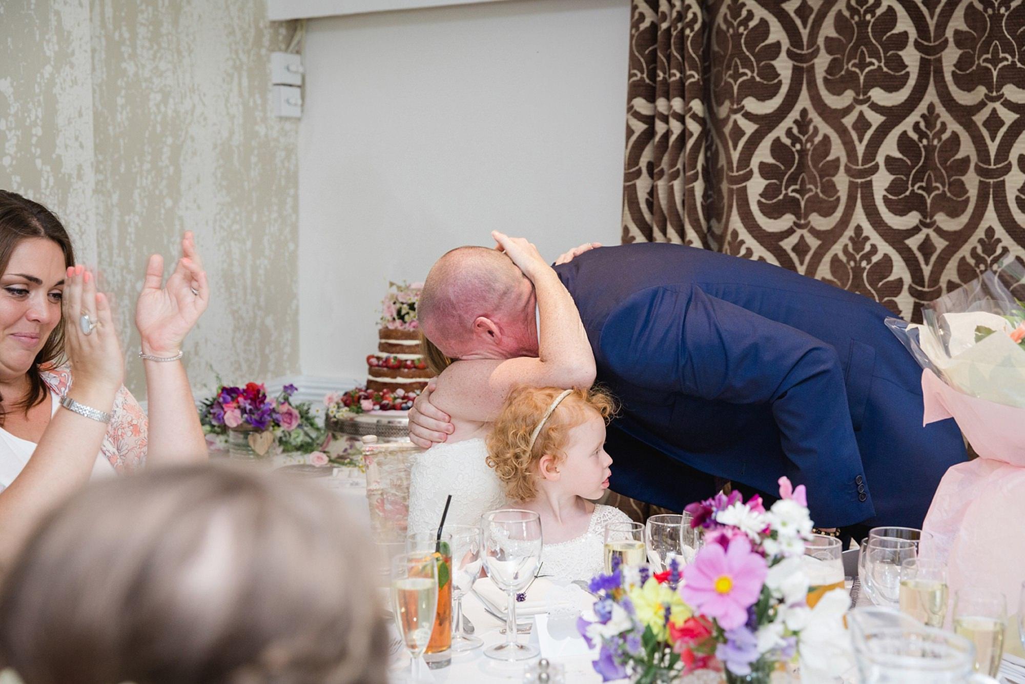 Mill House hotel wedding photography bride hugging groom