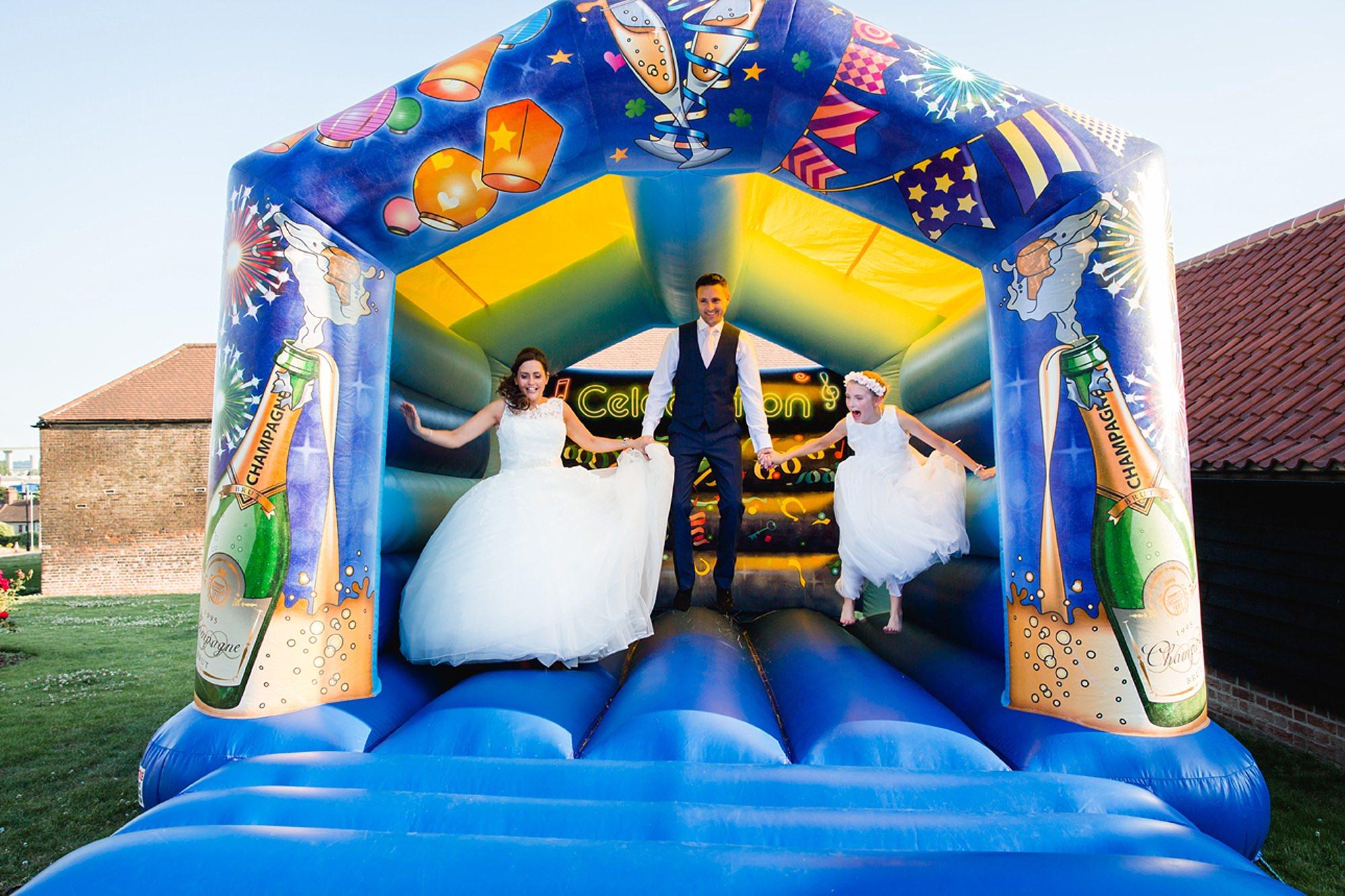 High House barns wedding photography bride and groom on bouncy castle