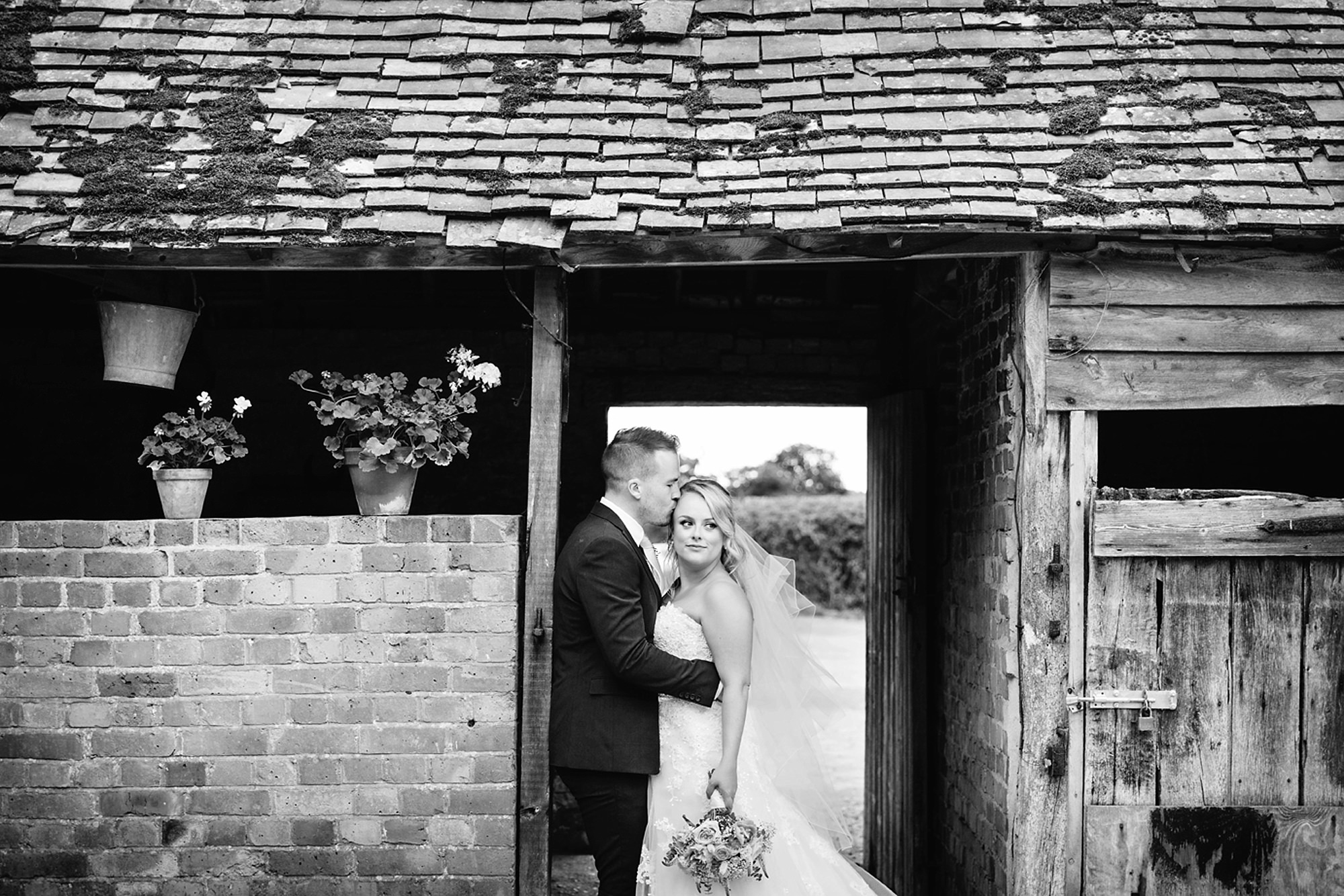 Old Greens Barn Newdigate wedding photography groom kissing bride