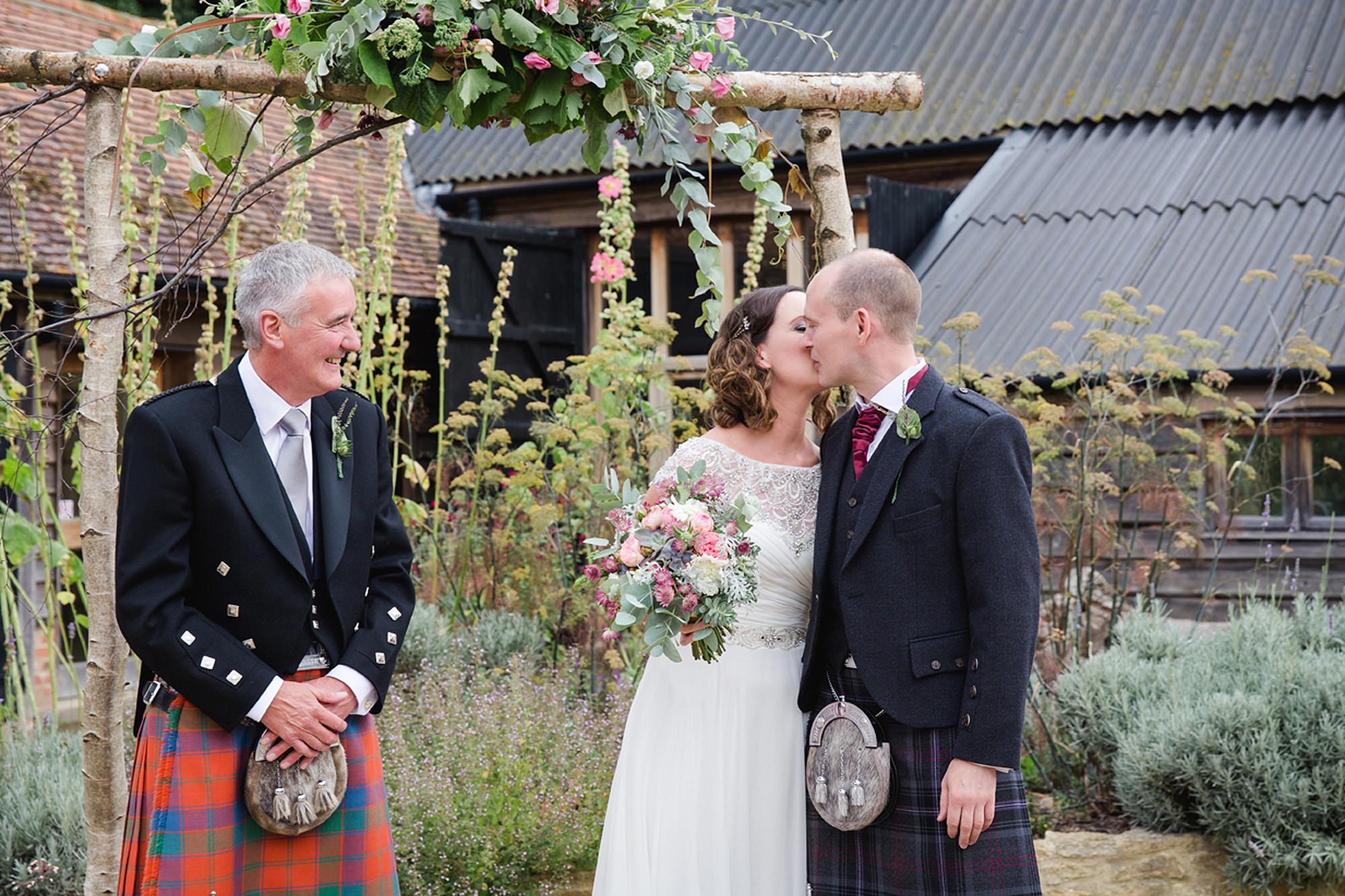 outdoor humanist wedding photography groom kisses bride