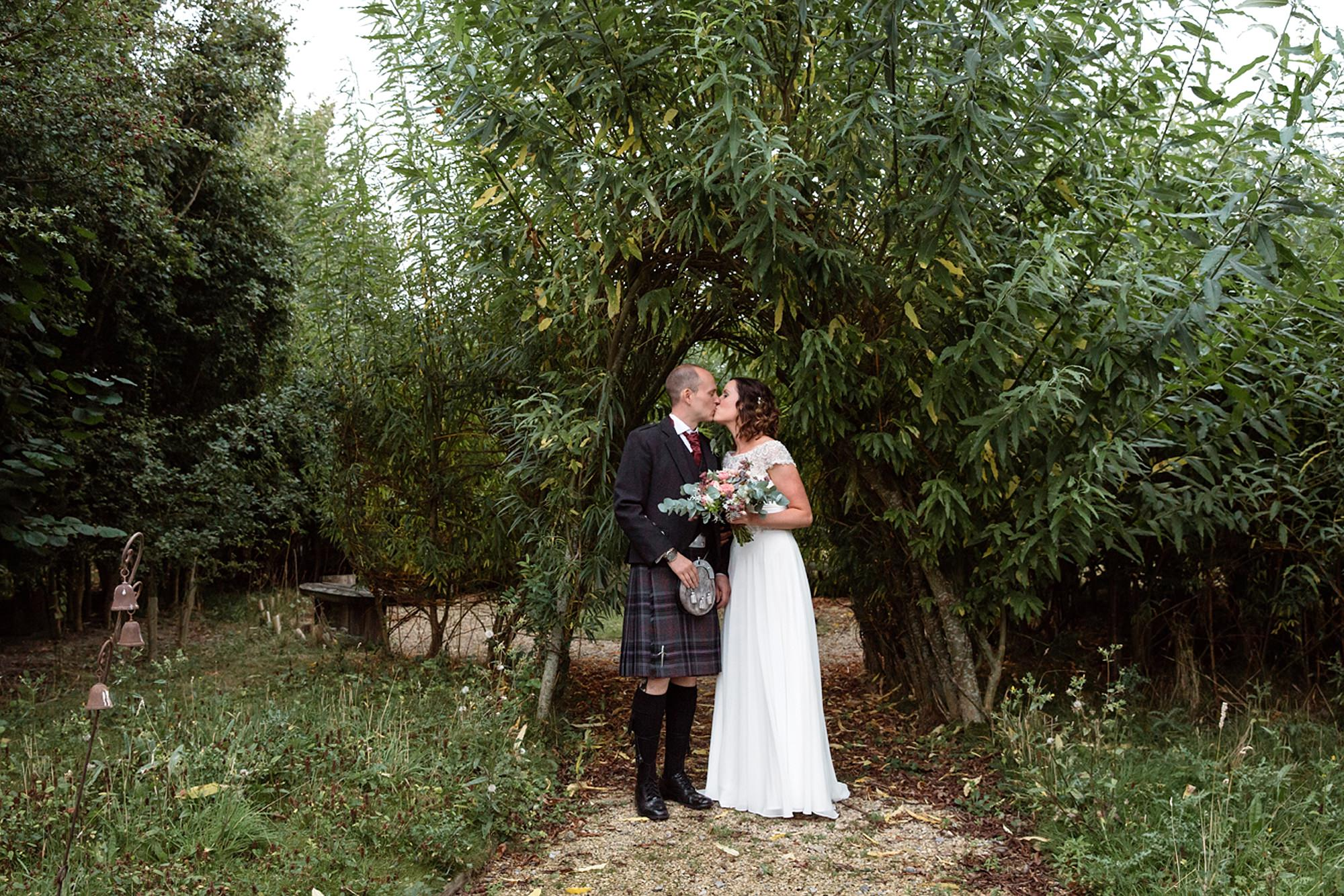 outdoor humanist wedding photography bride and groom kiss under tree structure