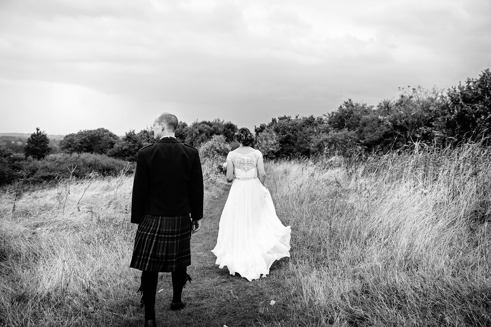 outdoor humanist wedding photography bride and groom walking in fields