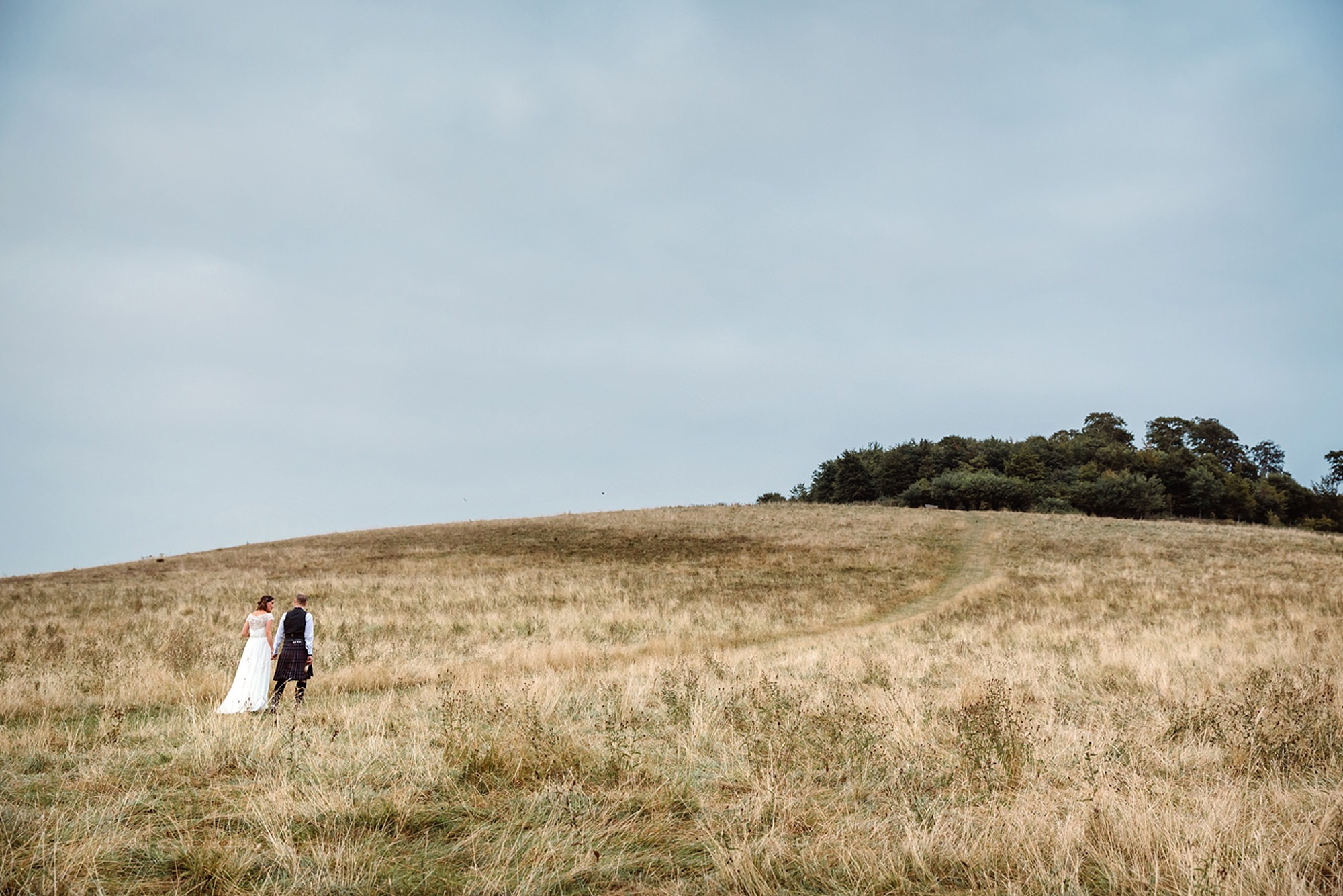 outdoor humanist wedding photography bride and groom walking up hill