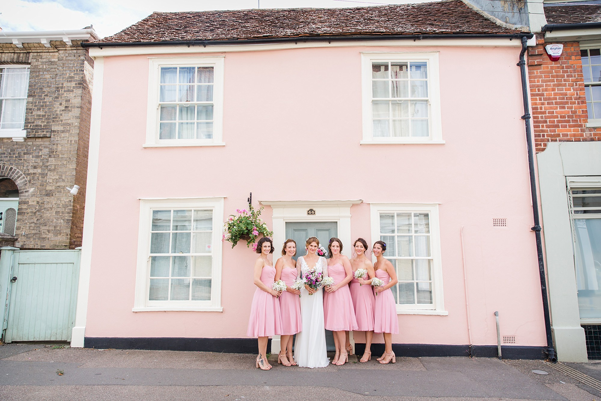 Marks Hall Estate wedding photography bride and bridesmaids outside pink house