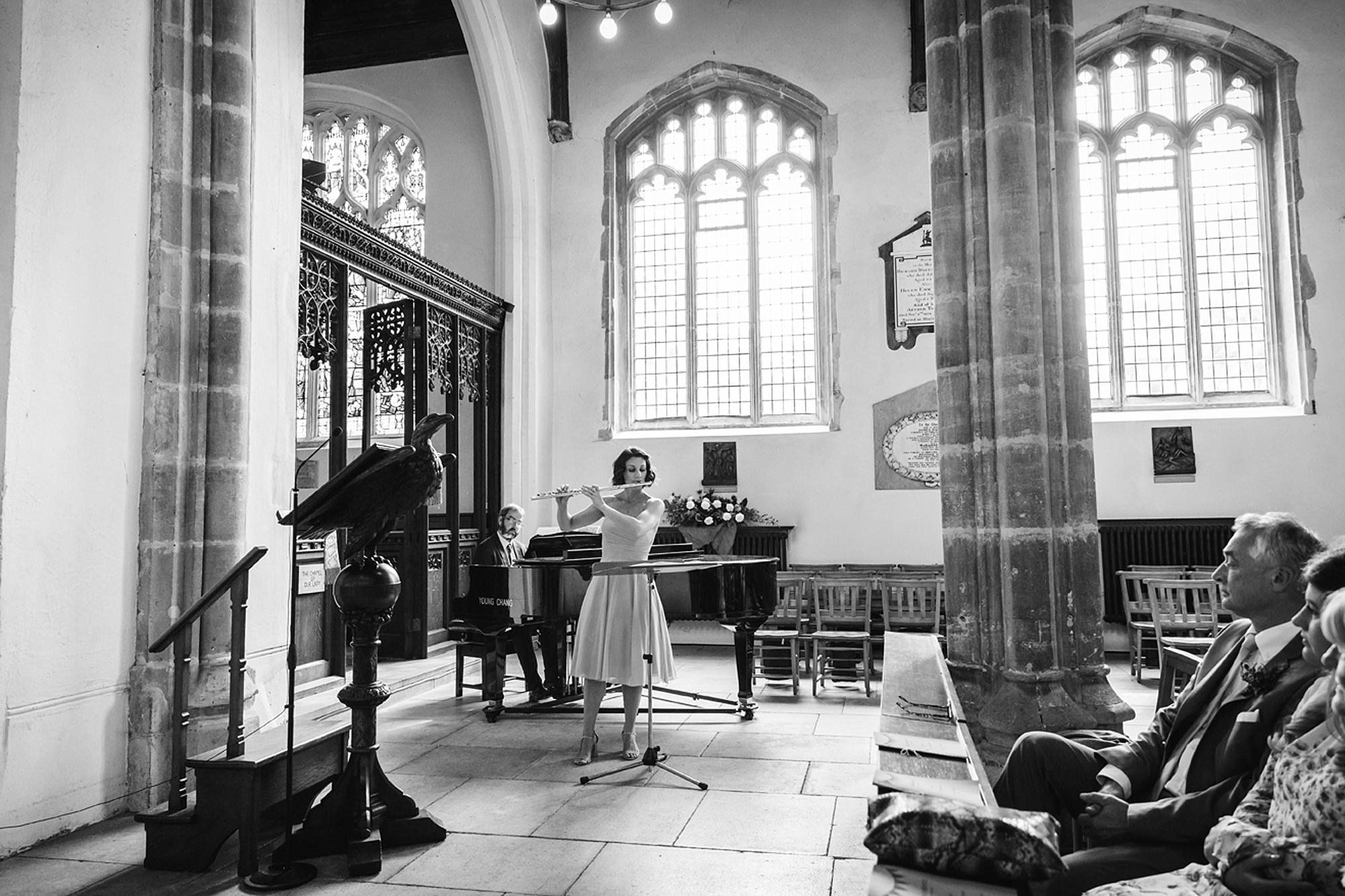 Marks Hall Estate wedding photography bridesmaid playing flute for wedding guests