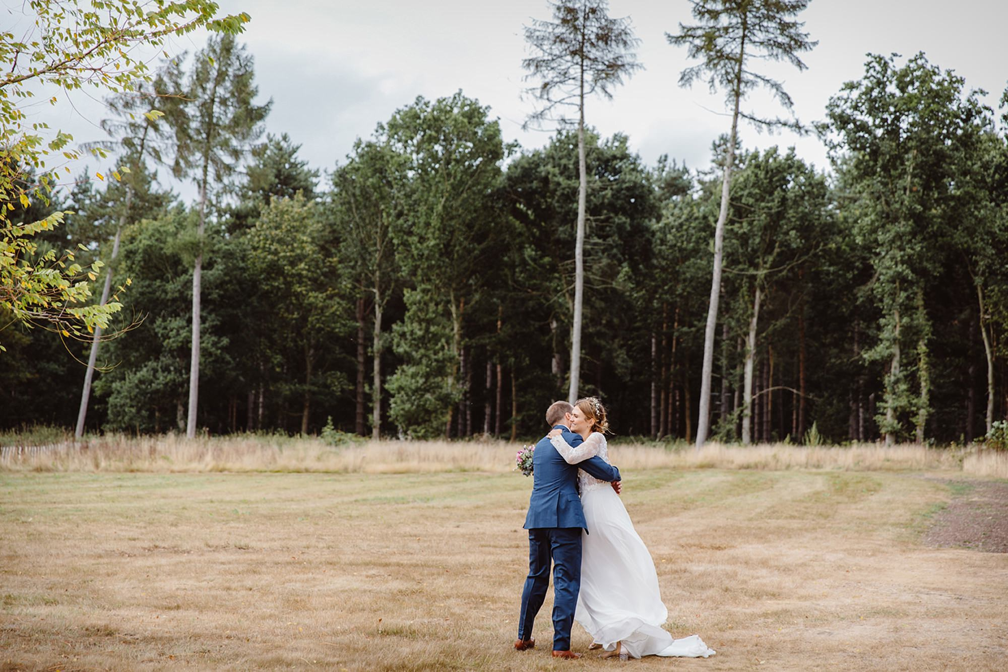 Marks Hall Estate wedding photography bride and groom hugging in field at marks hall estate