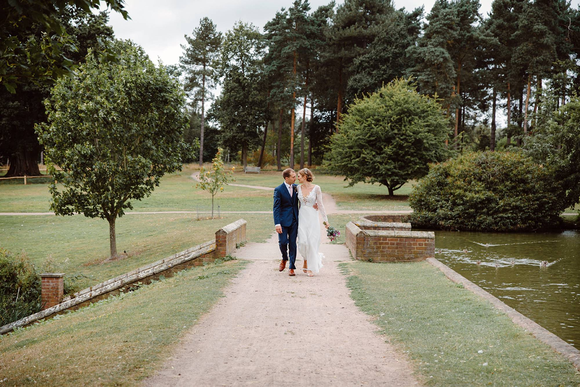 Marks Hall Estate wedding photography bride and groom walking and kissing