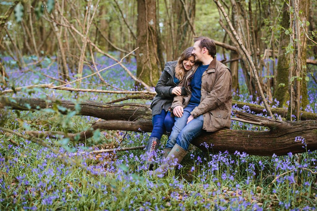spring engagement shoot couple sat on log with bluebells