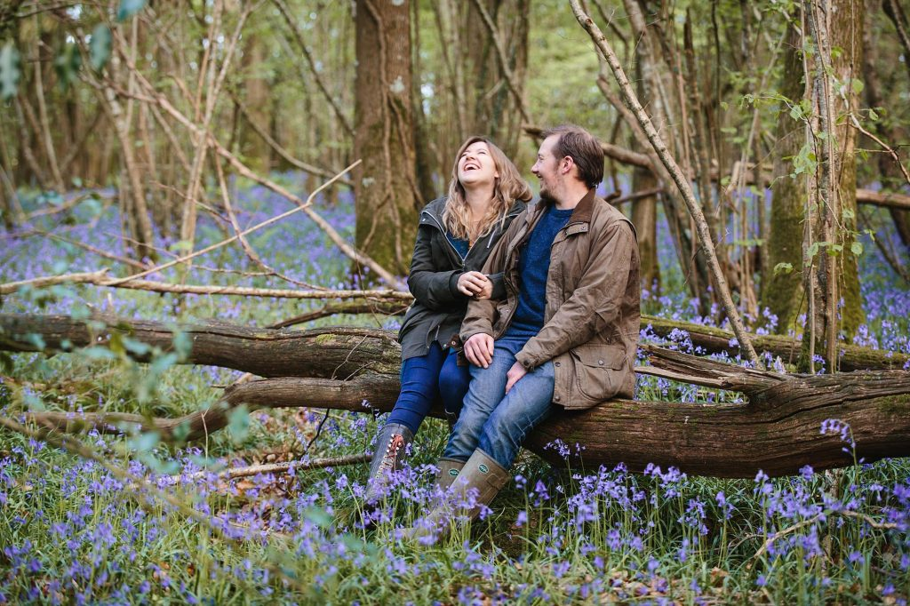 spring engagement shoot couple laughing on log