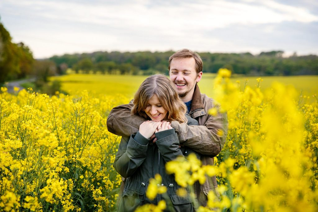 spring engagement shoot happy couple in field