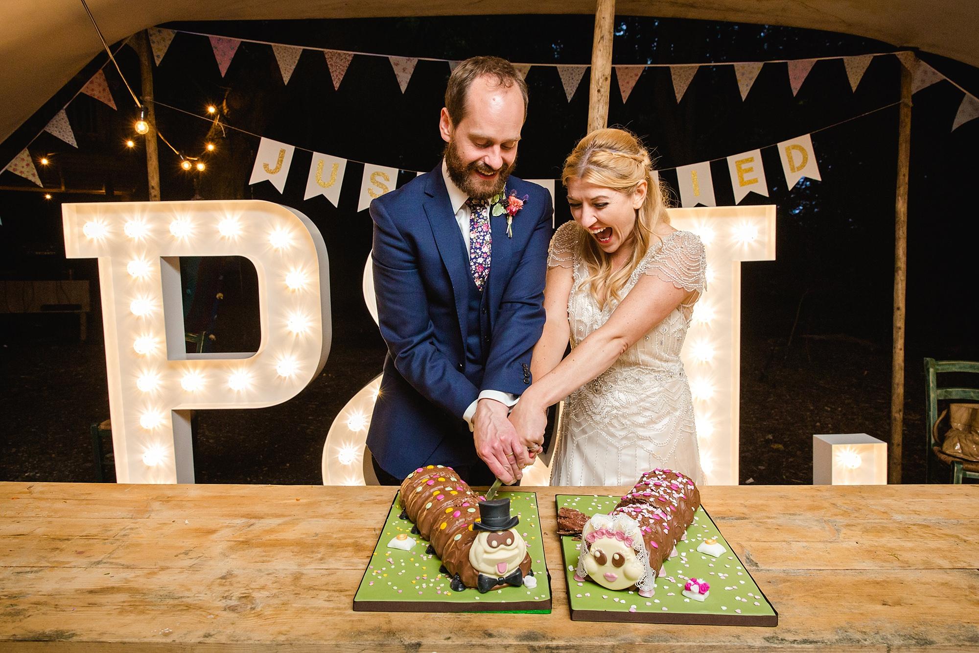 Woodland Weddings Tring bride and groom cut caterpillar cake