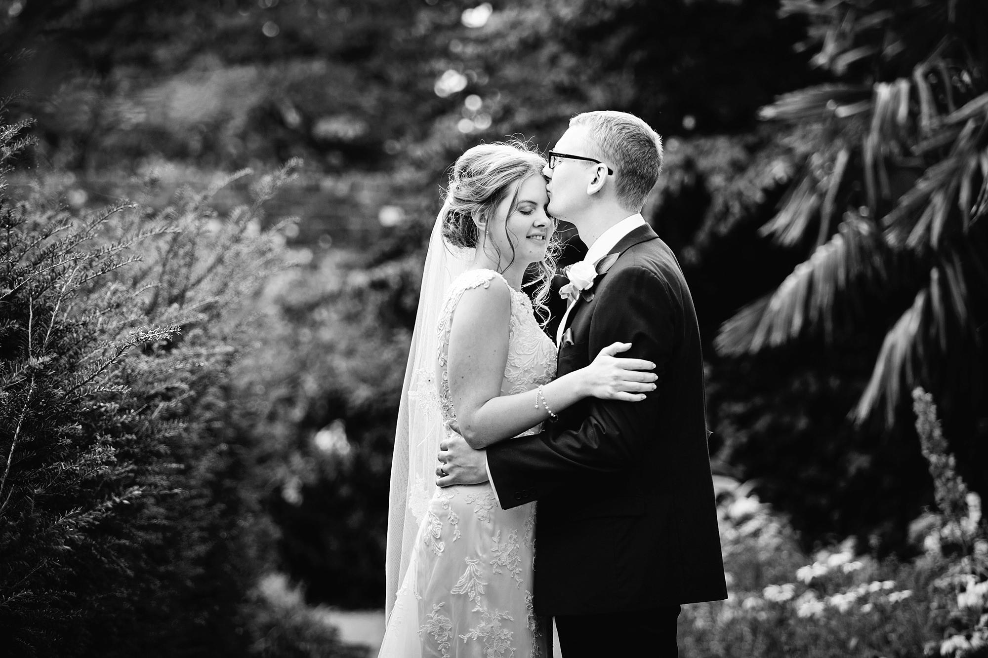 Canon Lane Chichester wedding groom kisses bride in bishops garden