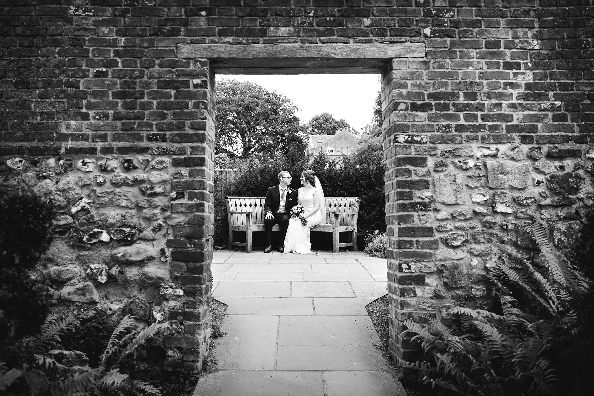 Canon Lane Chichester wedding bride and groom on bench outside cathedral