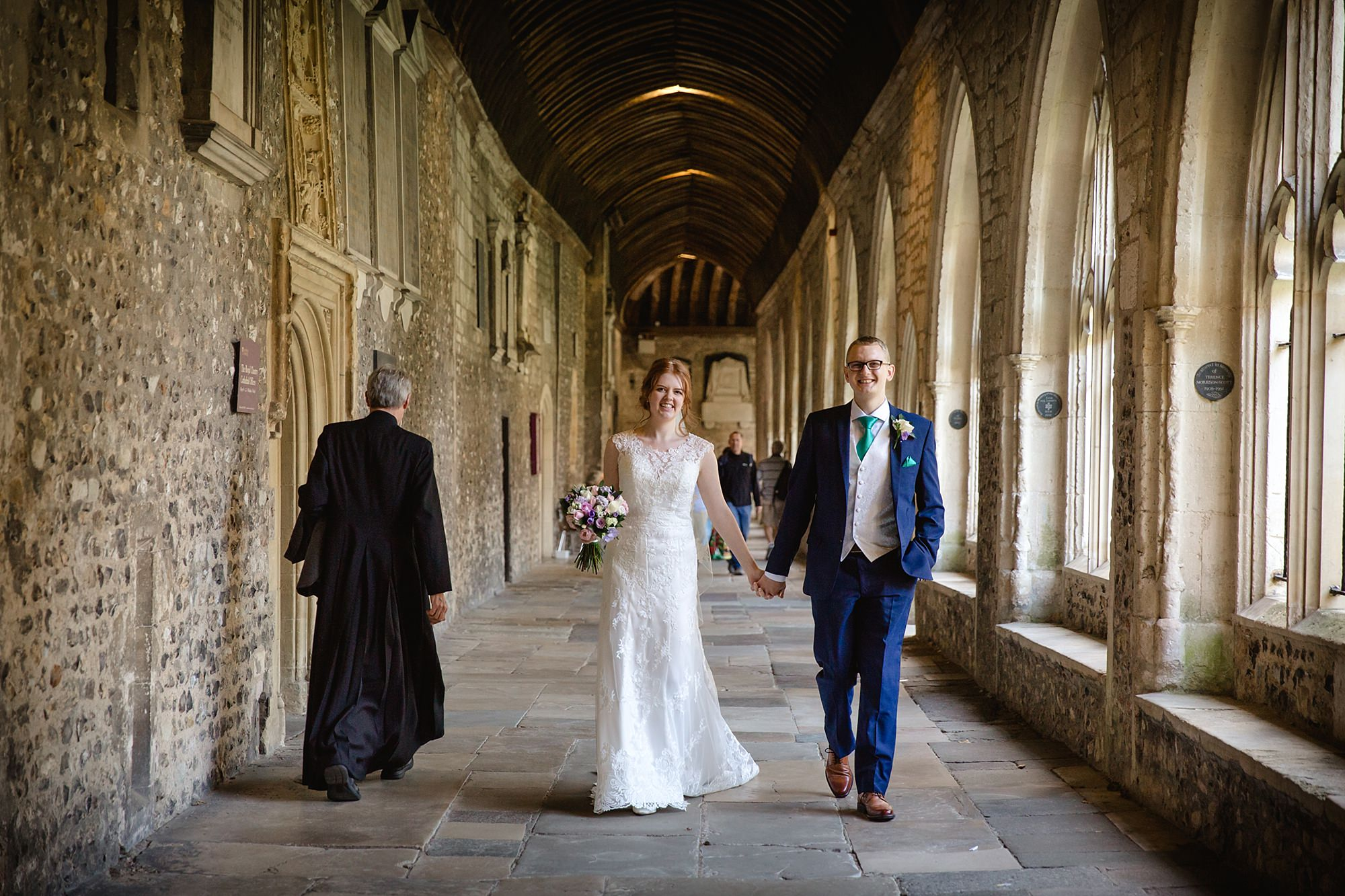 Canon Lane Chichester wedding bride and groom walk through Chichester cloisters