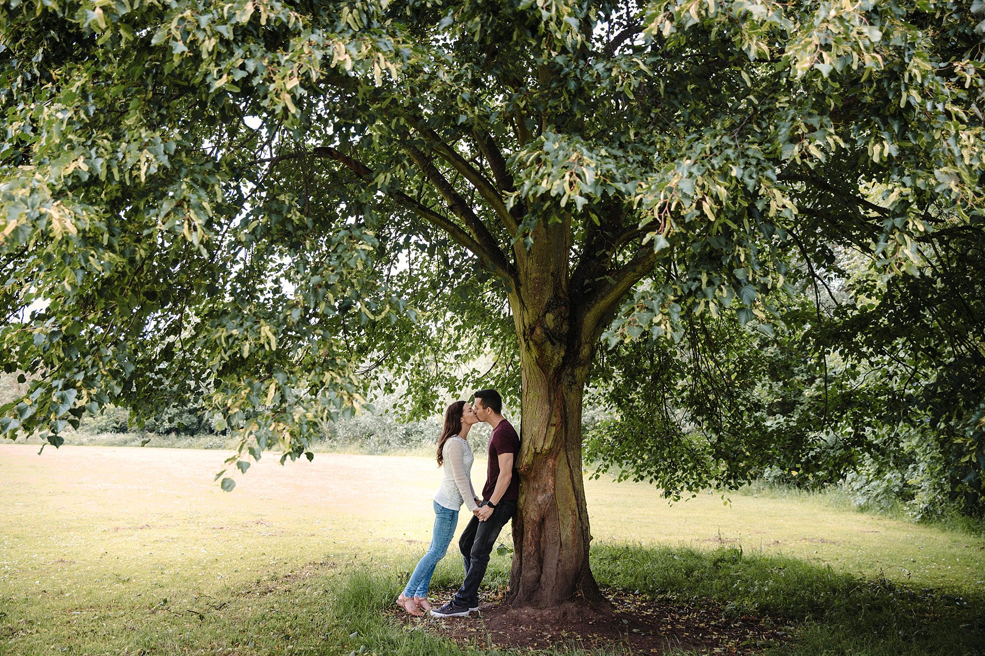 Countryside engagement photography couple kissing under tree