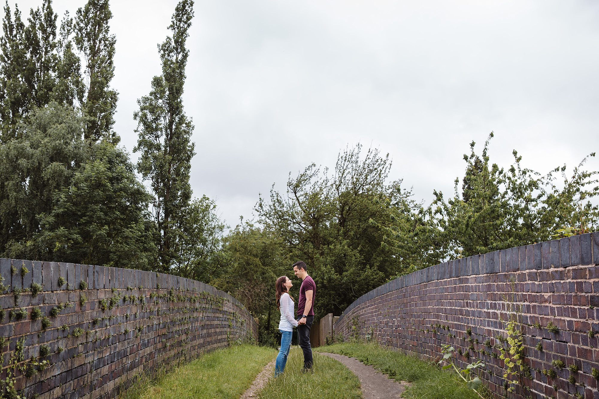 Countryside engagement photography couple stood on bridge