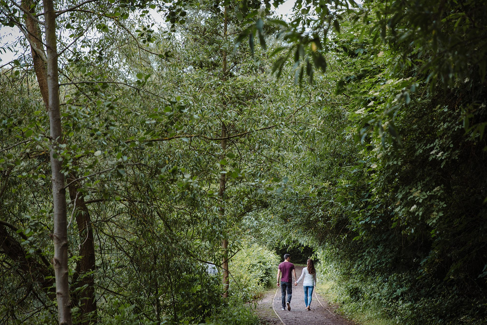 Countryside engagement photography a couple walk through tree path